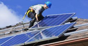 man installerar solceller på tak efter ett solcellslån